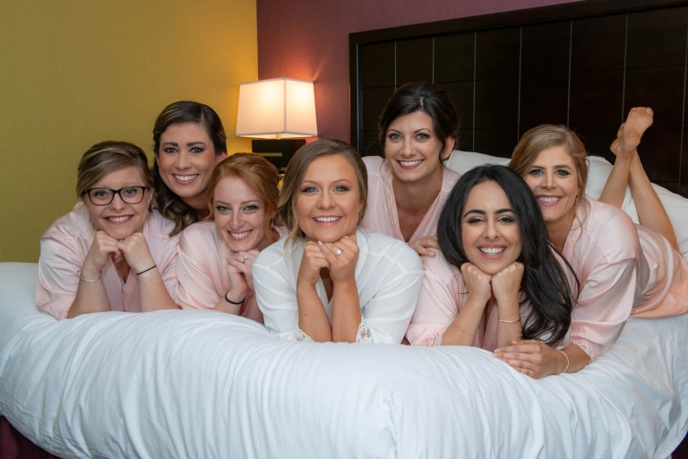 bride and bridesmaids picture on the bed