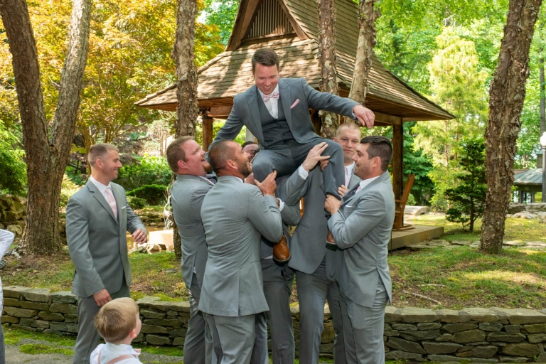Groomsmen hold the groom up